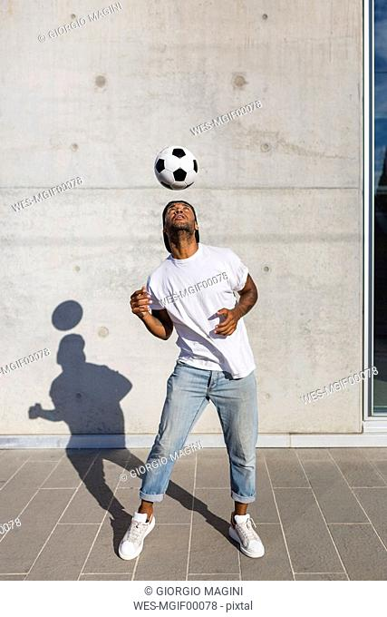 Young man playing with soccer ball in front of concrete wall