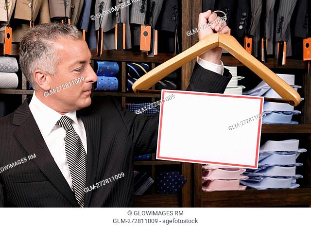 Businessman holding a hanger with blank signboard in a clothing store