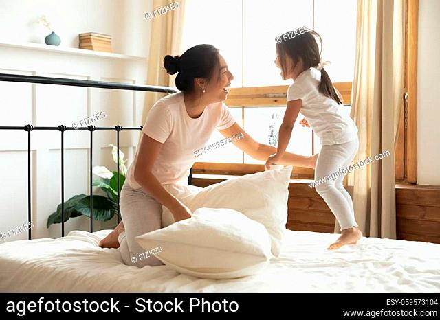 Excited vietnamese ethnicity female family in pajamas having fun on comfortable bed, playing pillow fight, enjoying energetic morning time after waking up...