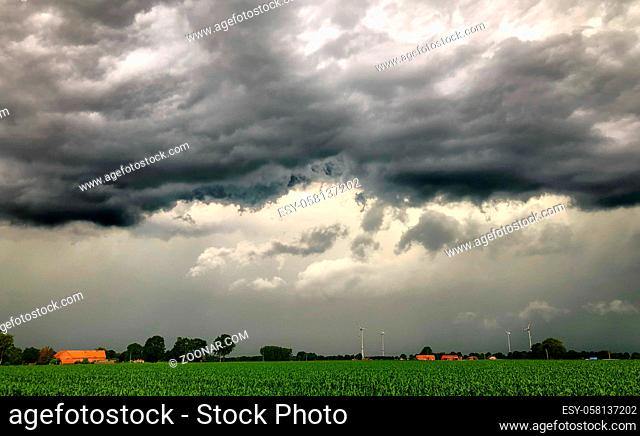 Threatening dark rainy clouds are covering a rural landscape, showing the Overcast and gloomy sky above the countryside creating a beautiful and impressive...