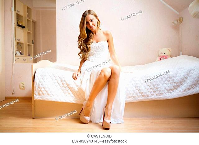 The bride sitting on a bed in wedding morning