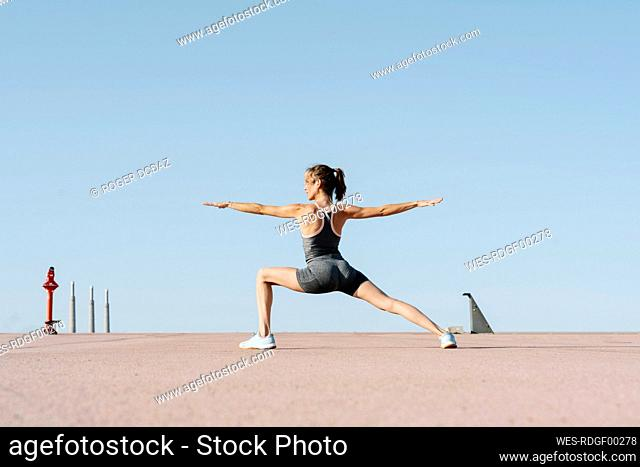 Female sportsperson practicing warrior position on a sunny day