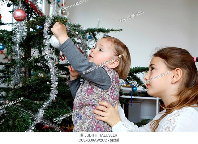 Side view of big sister helping girl decorate christmas tree