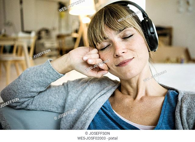 Relaxed woman with closed eyes listening to music with headphones