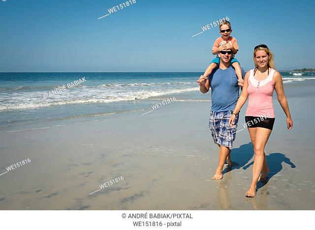 Family of 3 enjoying walk on the beach, Riviera Nayarit, Mexico