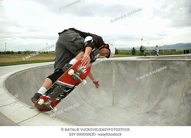 Skateborader doing bowl trick in Colorado Skate Park