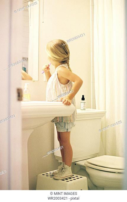 Young girl standing on a stool in a bathroom, brushing her teeth