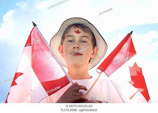 Young boy holding Canada Day flags, Smithers, British Columbia