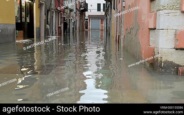 "A woman walking out from her home in Castello Quarter during the so called """"acqua alta"""" high tide. Venezia. Italy"