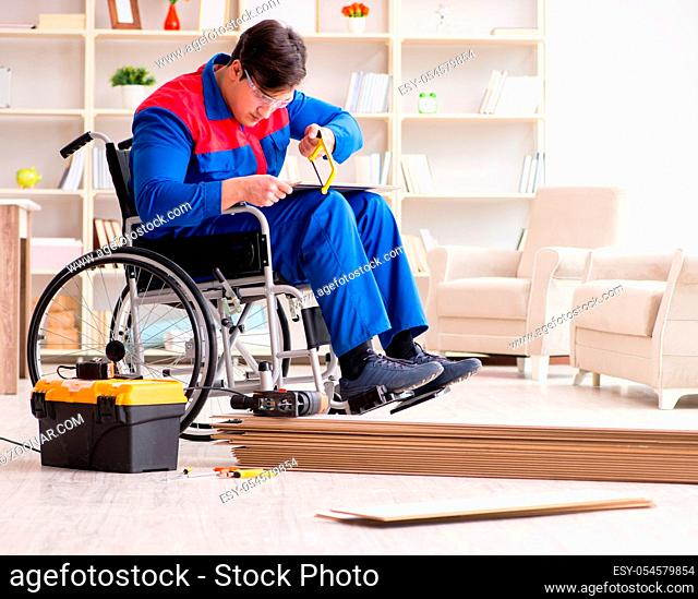 The disabled man laying floor laminate in office