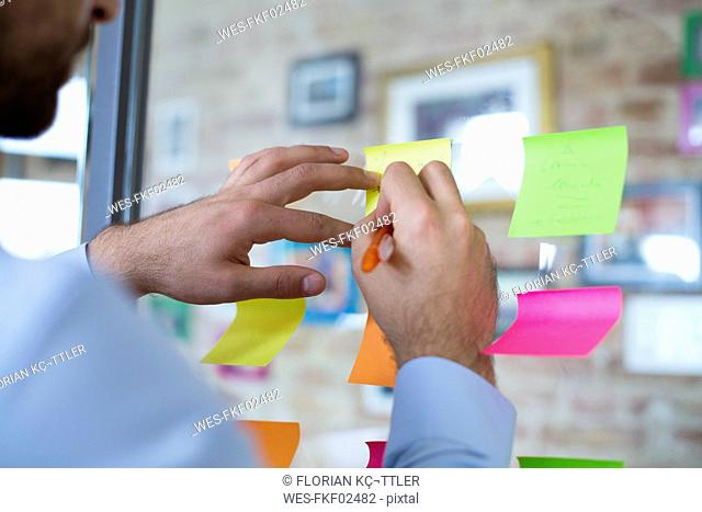 Close-up of man in office writing on adhesive note on glass wall