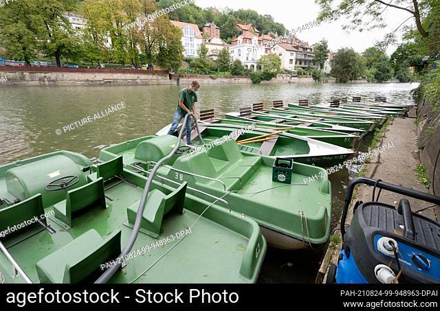 24 August 2021, Baden-Wuerttemberg, Tübingen: An employee of a boat rental Tübingen on the Neckar pedal and rowing boats for rent