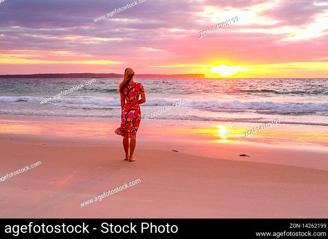 Woman standing on the seashore watching the sunrise. Its reflection in the wet sand. She is wearing a beach dress that is flowing in the breeze
