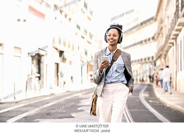 Smiling young woman with headphones and mobile phone in the city on the go, Lisbon, Portugal