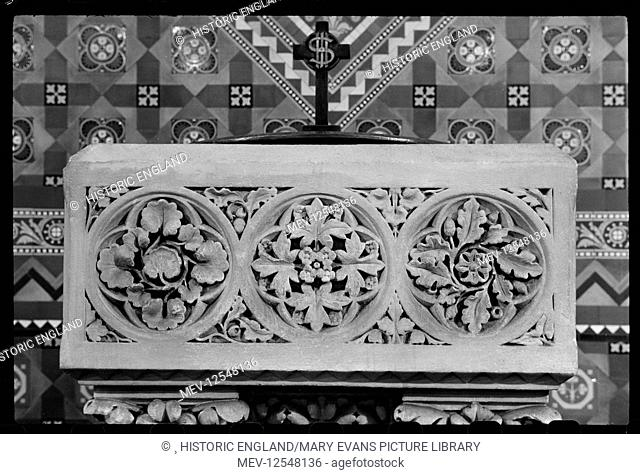 A detailed view of one side of a square font bowl, with quatrefoil carvings of foliage in roundels, and a partial view of the cross finial of the font cover...