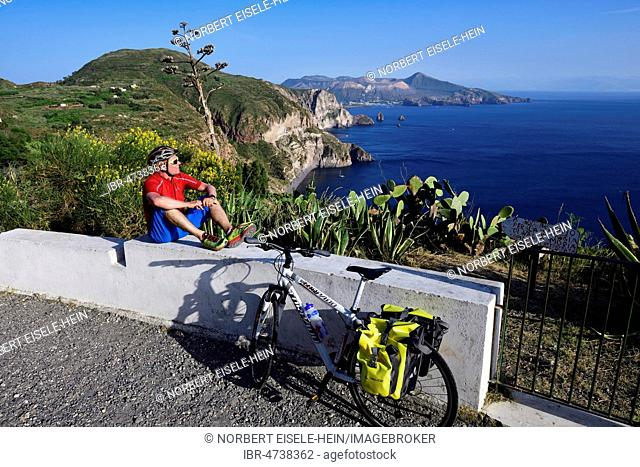 Cyclist pausing on the Belvedere Quattrocchi with a view over the rocks Faraglione on the island Vulcano, Pianoconti, Lipari, Aeolian Islands, Sicily, Italy