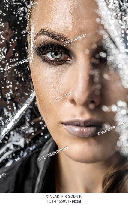 Portrait of beautiful woman in plastic against black background
