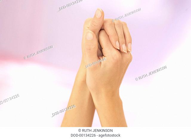 Wrapping hand around fist, squeezing