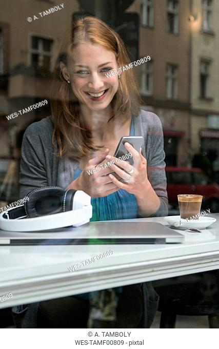 Portrait of smiling woman with smartphone in a coffee shop