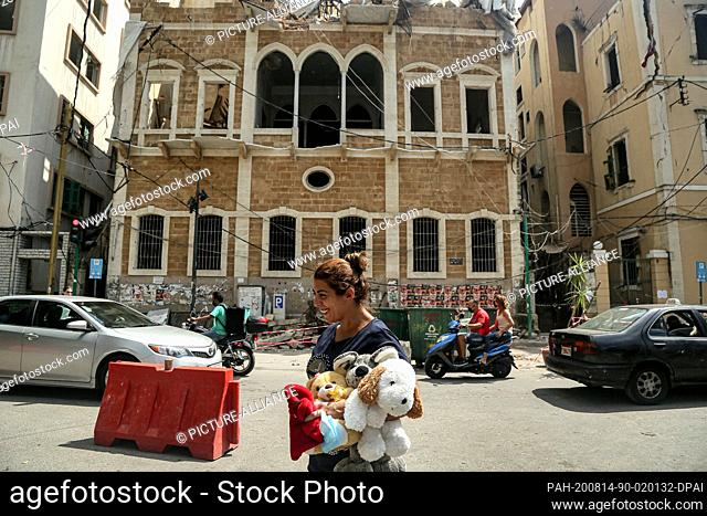 14 August 2020, Lebanon, Beirut: A woman walks past heavily damaged historical building in Mar Mekhail neighbourhood. The UNESCO is planning to lead an...