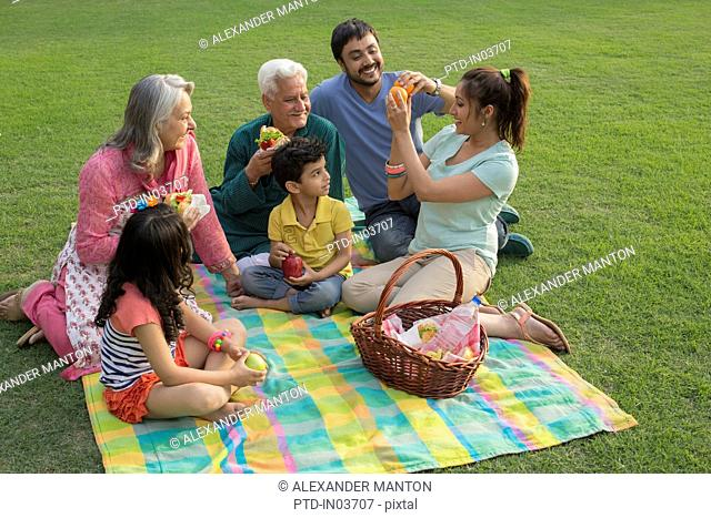 Mother handing out food at family picnic with children (4-5)