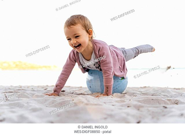 Portrait of laughing little girl balancing on Earth beach ball