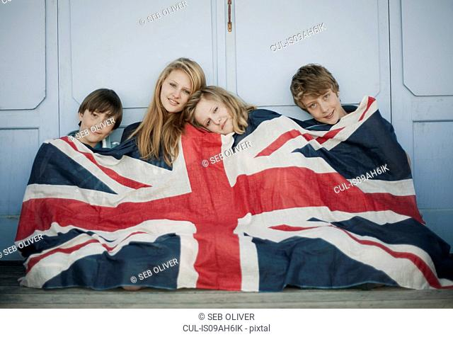 Portrait of brothers and sisters sitting on porch wrapped in union jack flag