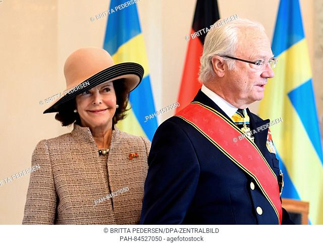 King Carl Gustaf and Queen Silvia of Sweden stand in front of the German and Swedish flags in Bellevue Palace in Berlin, Germany, 05 October 2016