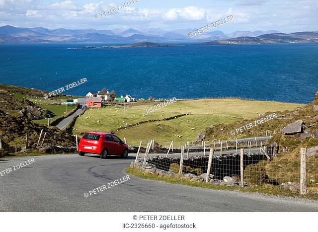 A car travels the road with a view of the ocean between eyeries and allihies;County cork ireland