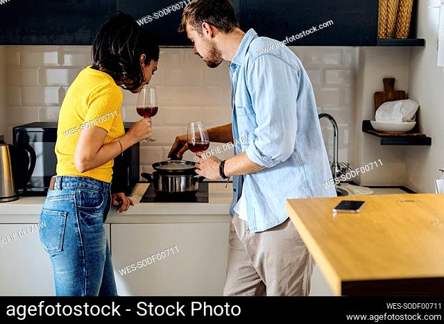 Young couple cooking and drinking wine in the kitchen at home together