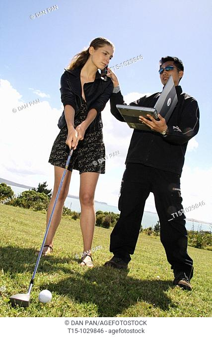 woman golfing talking on phone and looking at a laptop