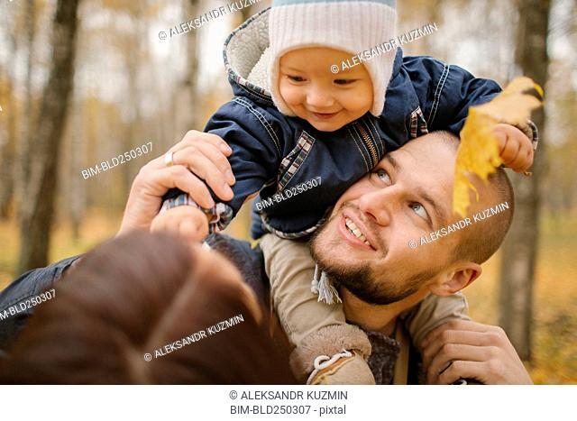 Middle Eastern father carrying baby son in autumn