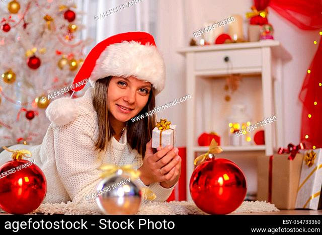 Happy girl in Christmas dress lies on the floor near the Christmas tree with a gift
