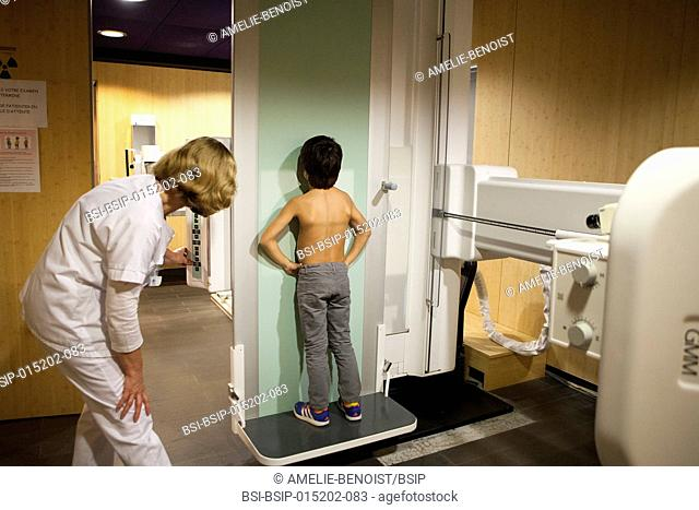 Reportage in a radiology centre in Haute-Savoie, France. A technician positions a young patient for a pulmonary x-ray