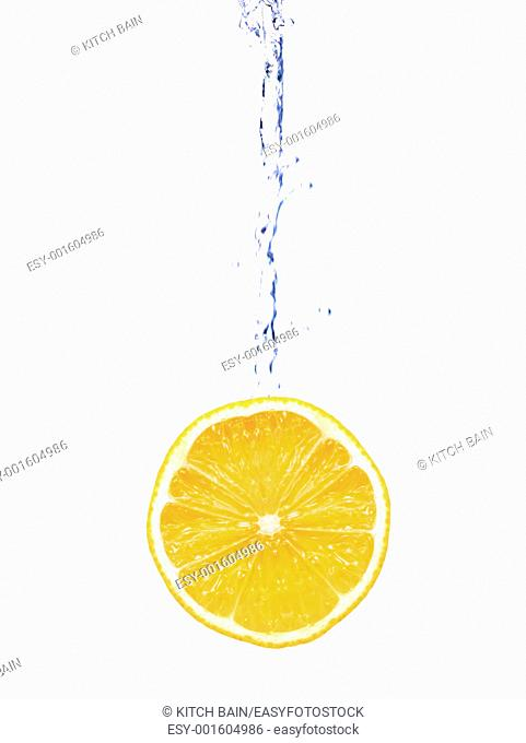 Citrus fruit and flowing water isolated against a white background