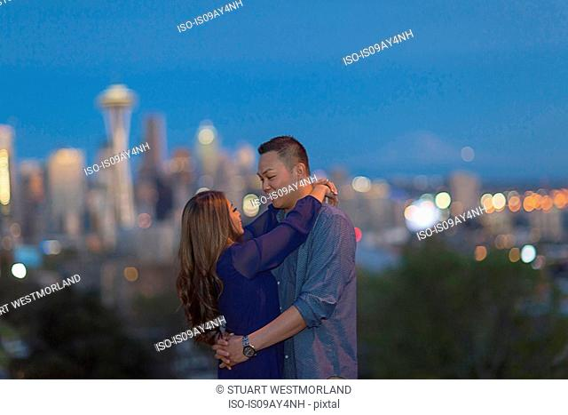 Couple hugging, city skyline in background