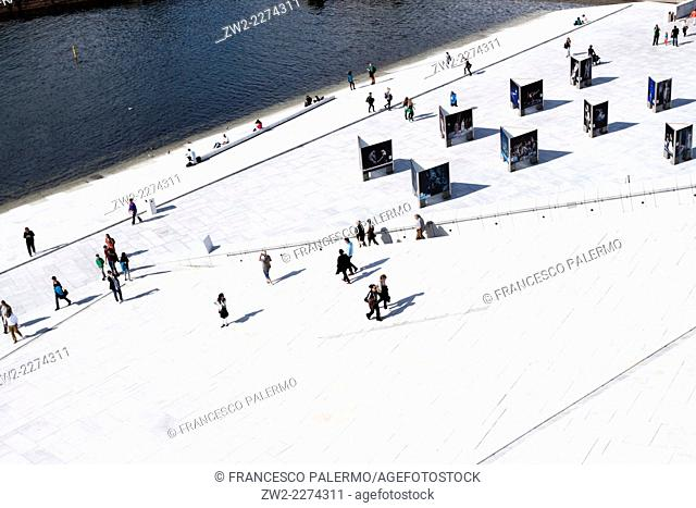 People moving on roof of exterior of Opera House in a summer day. Oslo, Ostlandet. Norway