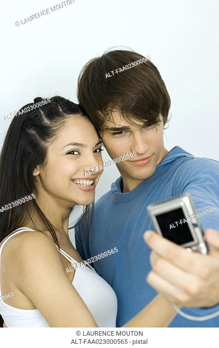 Young couple taking self portrait with digital camera, woman smiling at camera