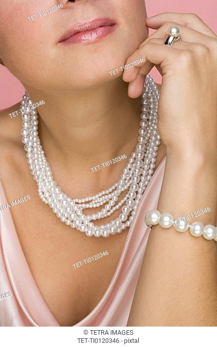 Close up of woman wearing pearls