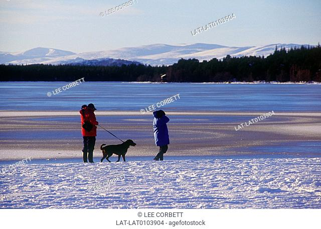 Glenmore. Snow on mountains. Lake,water. Snow on shore. Two people in coats. Dog