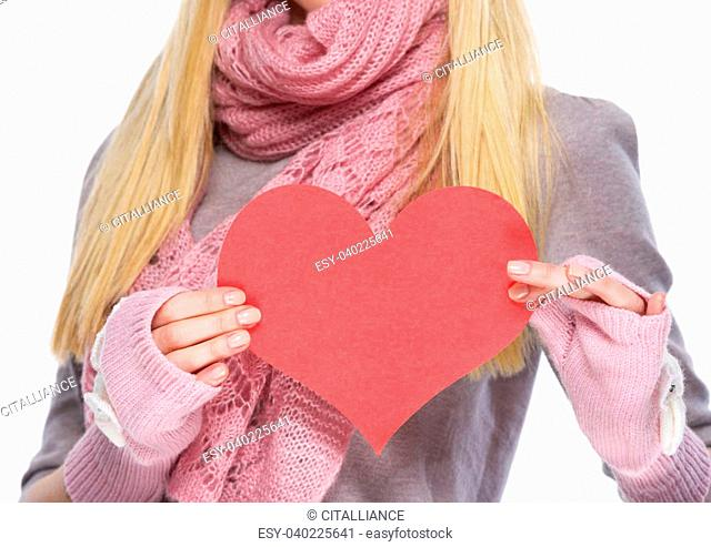 Closeup on heart shaped postcard in hand of teenager girl in winter gloves and scarf