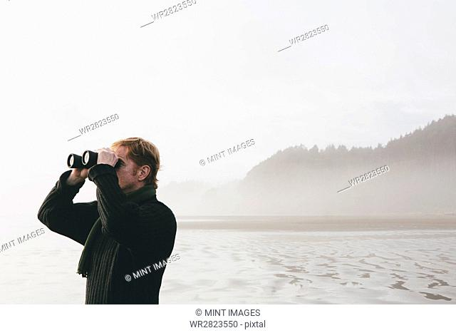 Middle aged man standing on a beach, looking through binoculars at Seabrook, Washington, USA