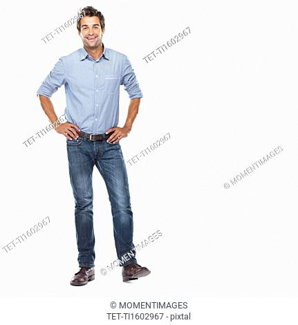 Studio shot of young man standing with hands on hips and smiling