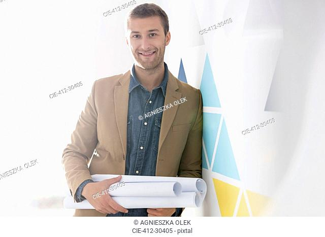 Portrait confident architect holding blueprints