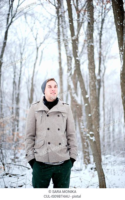 Young man standing in snow covered forest, Ontario, Canada