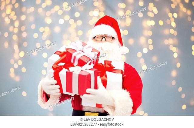 christmas, holidays and people concept - man in costume of santa claus with gift boxes over lights background