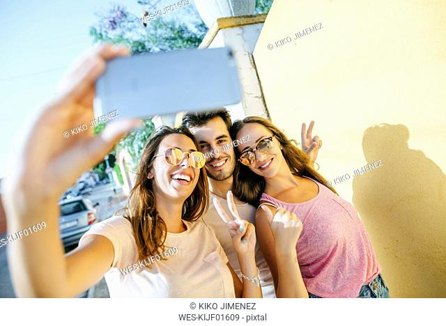 Friends taking a selfie with smartphone on the street