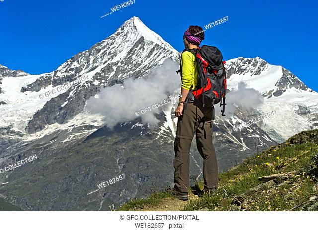 Woman with backpack looking at the Weisshorn peak above the Mattertal valley, Täschalp, Valais, Switzerland