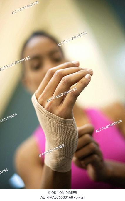 Woman with hand wrapped with bandage, low angle view