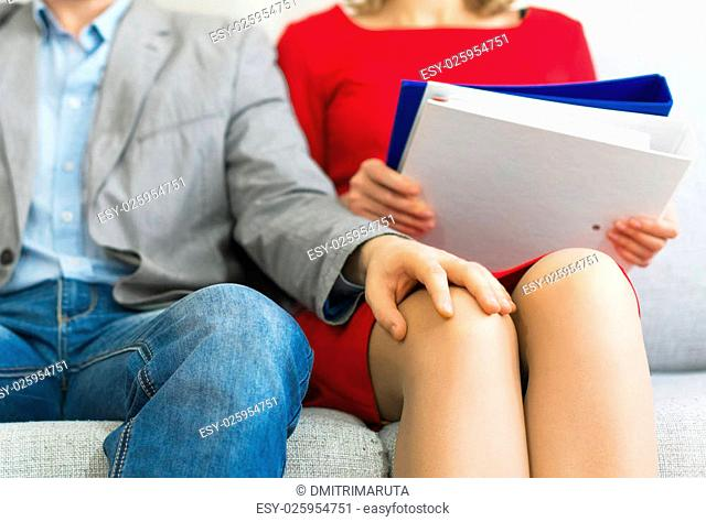 Sexual harassment at work. Man touching secretary's knee
